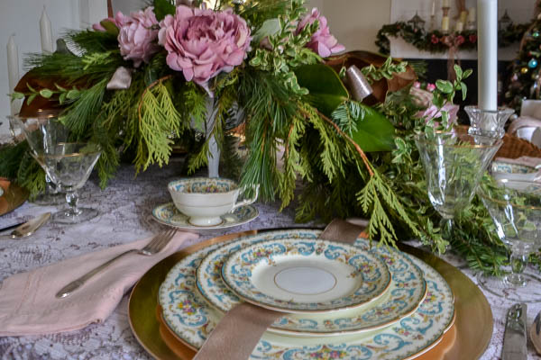 Evergreen Christmas table centerpiece with pink flowers