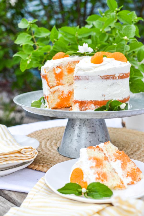 Double layered orange creamsicle poke cake with whipped cream and orange garnish