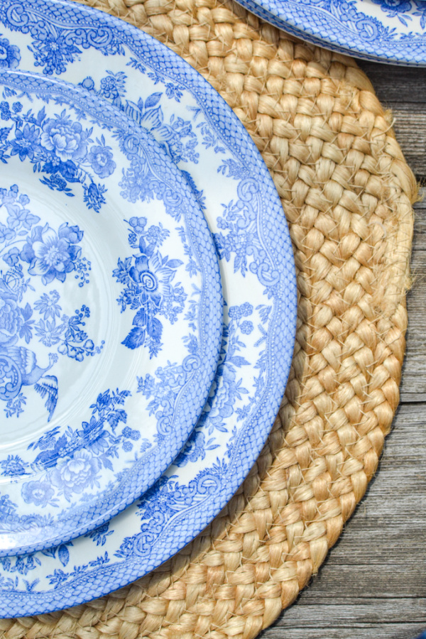 Blue and white dishes on a round rattan placement