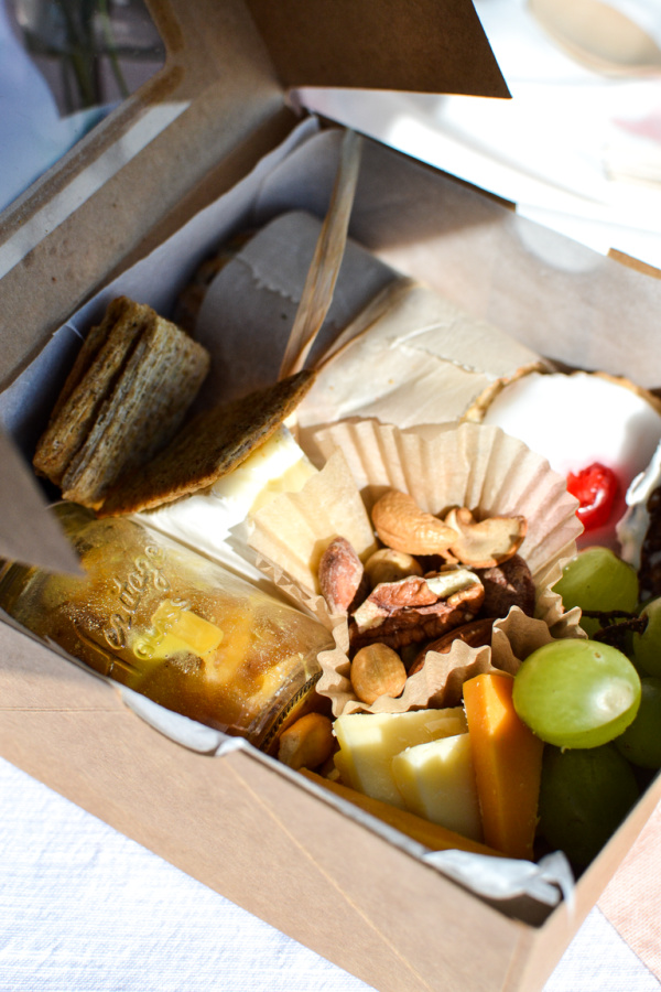 Sandwich, fruit, cheese and crackers in a box