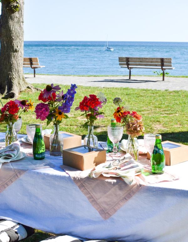 Sailboat passes a pretty picnic table near the lake