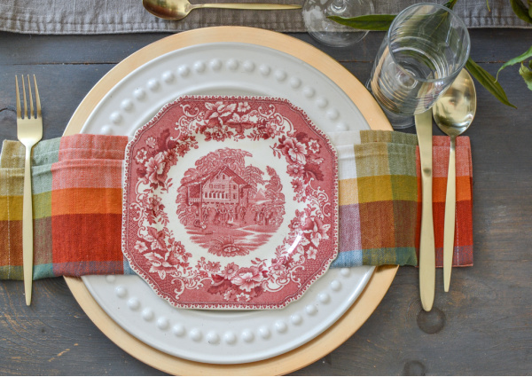 Pink transferware plates paired with plaid napkins create a Cozy Autumn table