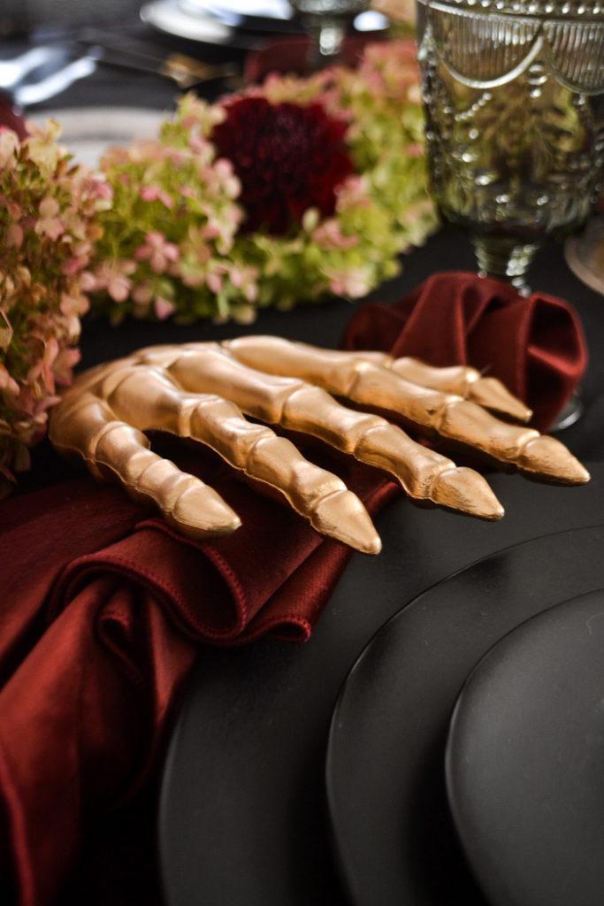 Gold painted skeleton hand holds a Merlot coloured velvet napkin