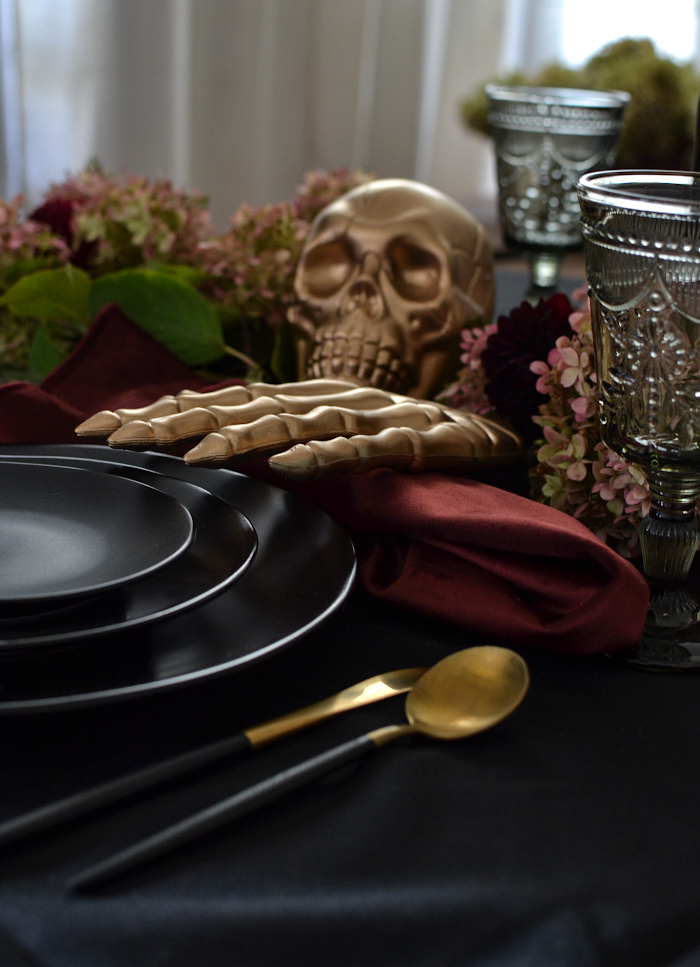 Gold skull and skeleton hand on a black Halloween table
