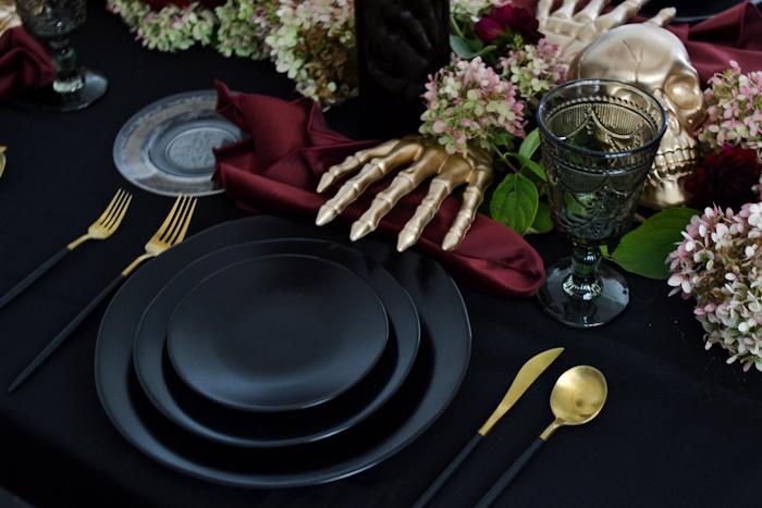 Black dinner plates, burgundy velvet napkin and gold skeleton hand